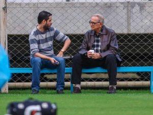 homens conversando campo de futebol